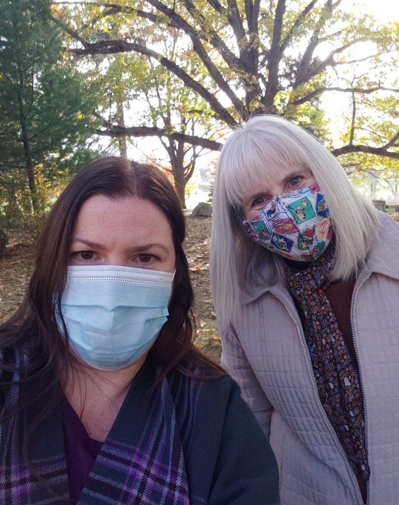 Two women in Oneida Community Cemetery for the tour wearing face masks